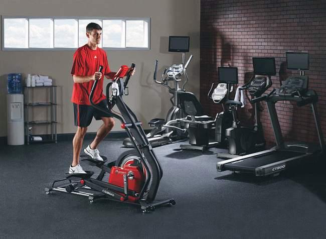Тренировка на эллипсоидном тренажере в спортзале